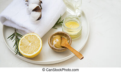 Organic skincare ingredients with towels and manuka honey, natural treatments ingredients with lemon, honey, balm salve, rosemary herb, spa still life setting