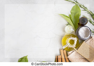 Organic skincare products flatlay with copy space, face oil bottle, olive oil and clay mask, natural soap on towel, top view on concrete background