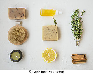 Organic skincare products flatlay with natural soap, oil bottle, brush, candle, rosemary herb, lemon and cinnamon, clean minimalist grey concrete background