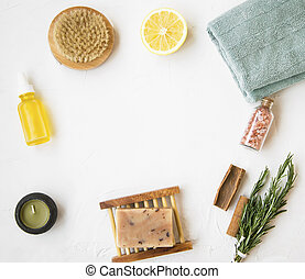 Organic skincare products flatlay with natural soap, oil bottle, brush, candle, salt, towel, rosemary herb, lemon and cinnamon with copy space