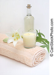Bath oil, towel and relaxing candle for a soothing natural spa treatment or bath time
