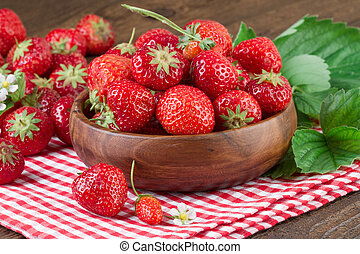 Strawberries in bowl on wooden background