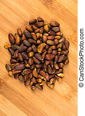 Organic unhulled pine nuts isolated on a wood background