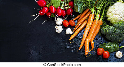 Organic vegetables harvest frame with tomatoes, carrots, mushrooms, radishes, spinach