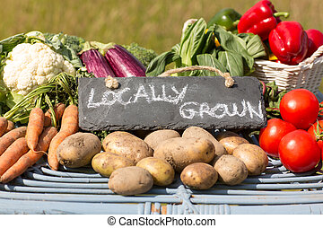 Organic vegetables on a stand at a farmers market with a...