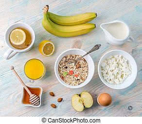 Organic vegetarian breakfast with oatmeal and fruits, hot tea with lemon, orange juice, topview