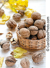 Organic walnuts in small basket on wooden background