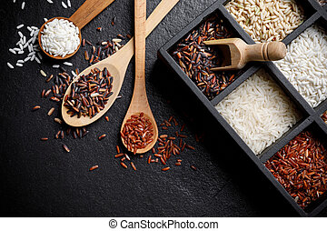 Organic White Rice, White rice, Jasmine rice, Black rice, Brown rice, Riceberry and Raw rice in wooden spoon and the boxes over black desk