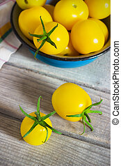 Organic yellow cherry tomatoes with water drops in blue...