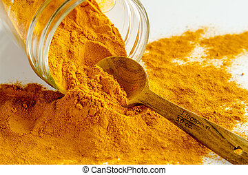 Close up of organic turmeric (curcuma) powder spilling out of glass jar with measuring spoon on white background