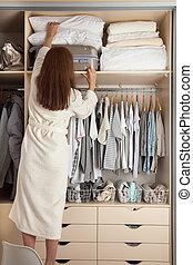 organiza, prateleira, mulher, wardrobe., mala, topo, jovem, armazenamento, travesseiros, mezzanine.