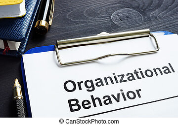 Organizational Behavior report on an office desk.