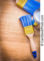 organized copyspace paint brushes and can on wooden board