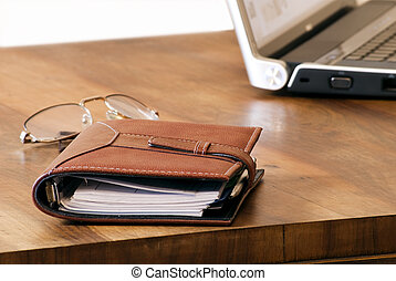 Organizer, glasses and laptop