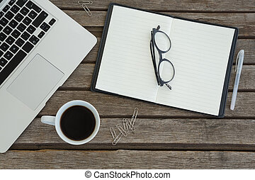 """Organizer, spectacles, pen, black coffee and laptop on wooden plank"""