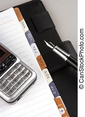 Organizer with fountain pen and mobile phone.