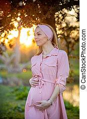 orgulhoso, vida, conceito, dela, mulher, luz, morno, grávida, parque, costas, olhando jovem, fundo, barriga, novo, retrato, amanhecer, feliz