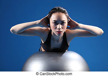 Oriental Asian woman back stretch on exercise ball