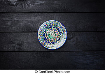 Oriental ceramic plate with beautiful colorful ornament. Top view dark wooden background