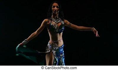 Oriental girl dancing on black background. Slow motion....