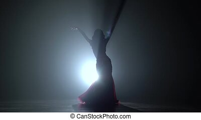 Oriental girl dancing on black smoke background. Sihouette -...