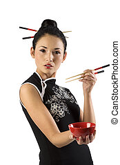 beautiful asian girl in japanes dress and chopstick showing a red cup