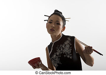beautiful asian girl in japanes dress eating oriental food from a red cup using chopstick