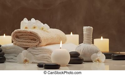 Oriental massage treatment composition. Towel, candles, flowers, stones and herbal balls. Spa procedures, meditation, wellbeing and aromatherapy concept.