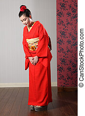 Oriental model in red Japanese kimono bowing - Respectful ...