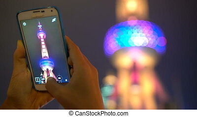 Oriental Pearl Tower Shanghai China travel tourist taking photo with smart phone at night at famous chinese tourist attraction destination. Close up of smartphone, focus change to background.