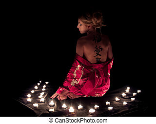 Beautiful blonde lady with hieroglyphs on back surrounded by candles