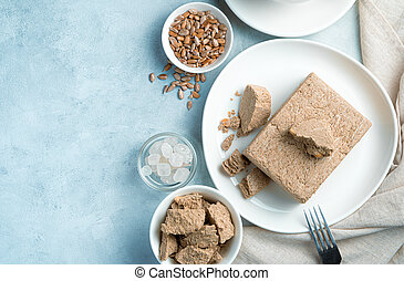 Halva, sugar, seeds on a blue background with space to copy.