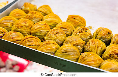 Oriental sweets pahlava with nuts, pistachio and honey on a tray