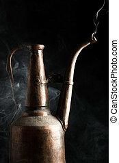 Oriental vintage brass pot with vapor against black backgrounds