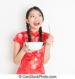 Oriental woman in red qipao eating with chopsticks