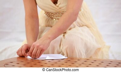Origami By Hand - A girl in a beautiful dress makes origami.