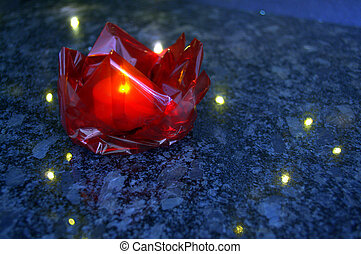A handmade red cellophane origami lotus with light
