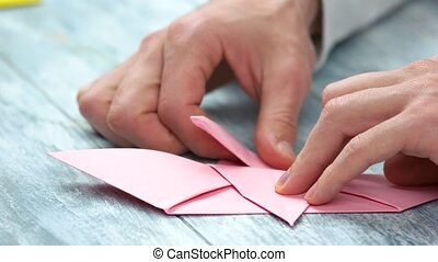 Origami crafting close up. Male hands making pink paper...
