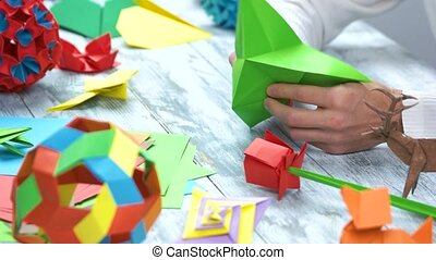 Origami crafts. Male hands making origami with green paper,...