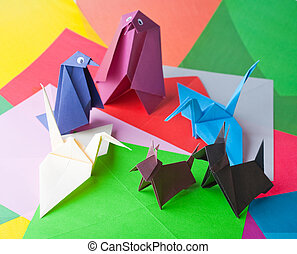 Origami. Figures of birds and animals against colour paper