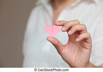 Origami heart in human hand.