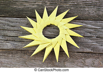 Origami yellow paper sun on wooden background