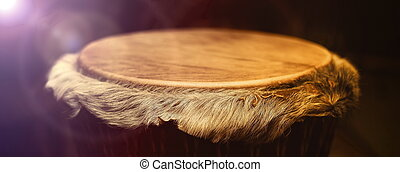 Original african djembe drum with leather lamina with beautiful hair in beautiful effect violet yellow light with dark background