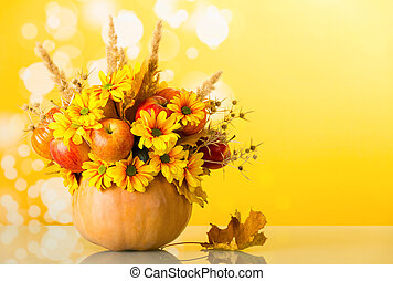 Original bouquet of apples, flowers and ears of corn in the pumpkin, on bright yellow