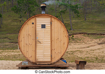 Original wooden bath in the form of a barrel. Mobile compact bathhouse on the shore of Sarai beach, Olkhon island Russia