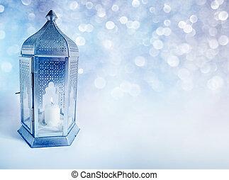 Ornamental Arabic lantern with burning candle glowing at...