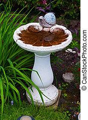 A white, concrete, ornamental garden bird-bath with decorative snail figure.