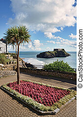 A picturesque and verdant ornamental garden planted with flowers and palm trees, set against a backdrop of St Catherine's Island and Castle Beach, Tenby.