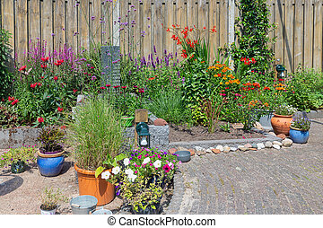 Ornamental garden with colorful plants in flowerbed and flowering pots