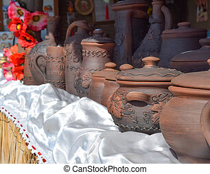 Ornamented clay pots. Dark brown dishes of baked clay.